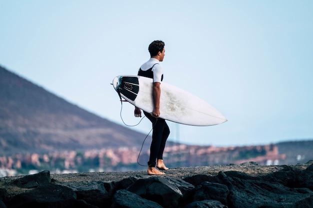 Ein teenager, der mit seinem surftisch unter dem arm ins wasser geht, bereit zum surfen - aktiver athlet geht zum training am wasser - mann mit neoprenanzug