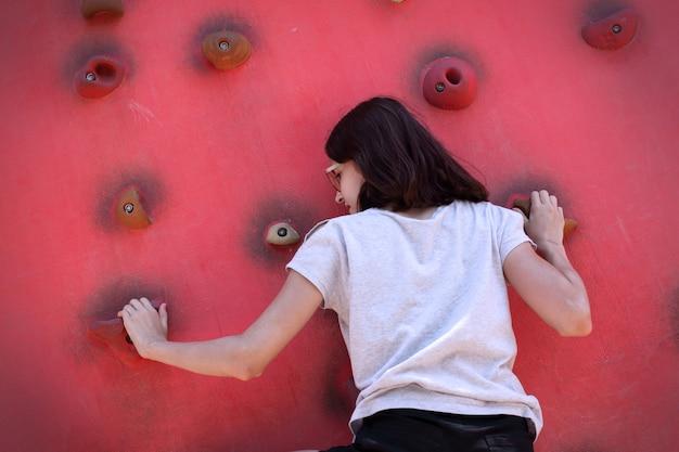 Ein teenager klettert an einer kletterwand