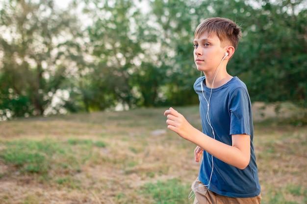 Ein teenager läuft in der natur mit kopfhörern, die musik hören