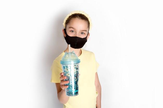 Ein teenager-mädchen in einer schützenden schwarzen kovid-19-maske ist aktiv am sport beteiligt. das konzept des lebens während einer epidemie. foto in hoher qualität