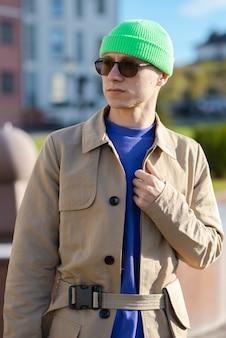 Ein teenager mit brille, die draußen vor einem gebäude steht und einen grünen hut und einen pullover trägt