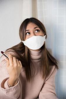 Ein teenager mit einer schutzmaske, der darüber nachdenkt, wie man einen lippenstift aufträgt