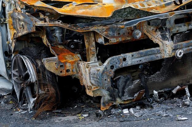 Ein teil des autos nach brandstiftung auf einem parkplatz in der nähe des hauses.