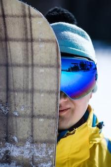 Ein teil des gesichtes des snowboarders ist von einem snowboard bedeckt