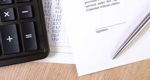 Ein teil des vertrags- oder vertragsdokuments, ein unterschriftenraum mit einem silbernen stift und einem taschenrechner.