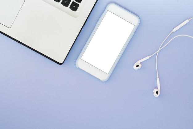 Ein telefon mit einem weißen bildschirm, einem laptop und kopfhörern auf einem blauen hintergrund. flat lay gadgets und platz für text.