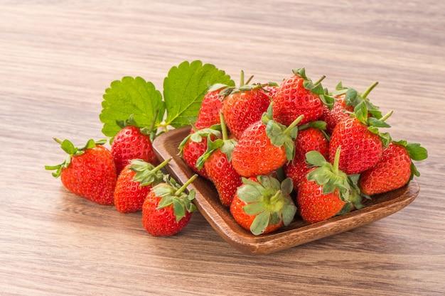 Ein teller der schönen erdbeeren lokalisiert auf hölzernem hintergrund, nah oben.