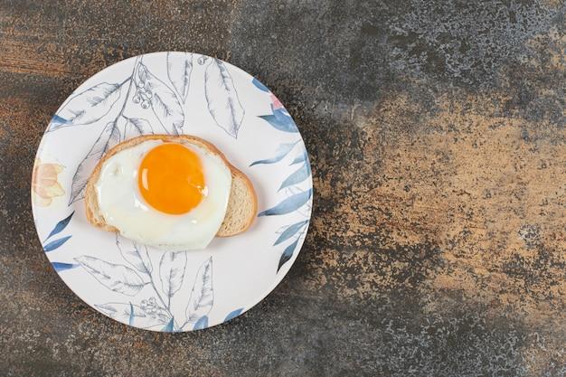Ein teller ei auf der weißbrotscheibe.