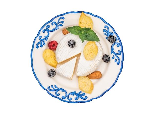 Ein teller mit camembert-käse, beeren und crackern auf einem weißen hintergrund. ein produkt aus natürlicher milch.