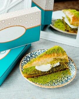 Ein teller mit dreieckig geschnittenem türkischem dessert mit pistazien- und vanilleeis Kostenlose Fotos