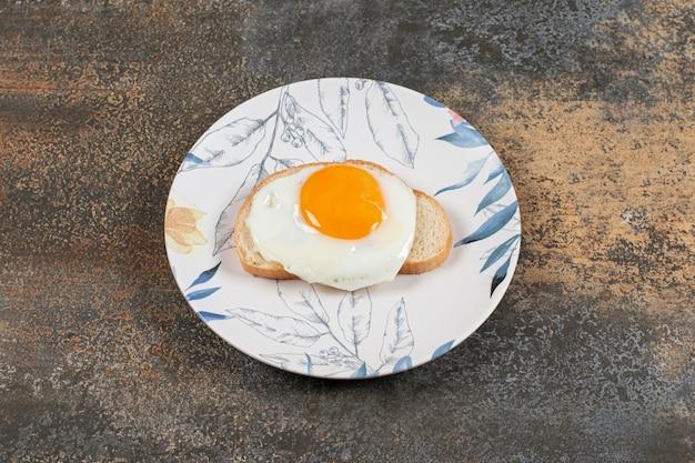 Ein teller mit ei auf der weißbrotscheibe.