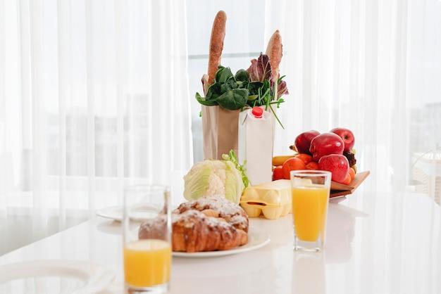 Ein teller mit essen auf einem tisch neben einem fenster, morgenfrühstückskonzept