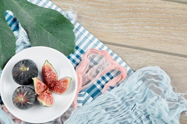Ein teller mit ganzen und in scheiben geschnittenen schwarzen feigen mit blauen und rosa tischdecken auf holztisch.