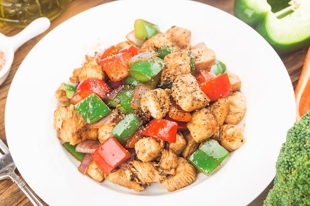 Ein teller mit gebratener hühnerbrust mit farbigem pfeffer