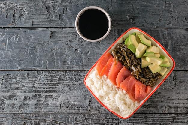 Ein teller mit hawaiianischem reis, avocado, lachs und seetang und weißer schüssel mit sojasauce auf einem schwarzen dunklen tisch. der blick von oben.