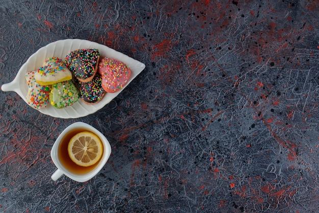 Ein teller mit herzförmigen keksen mit streuseln auf einer dunkelheit
