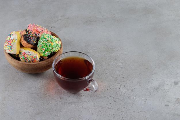 Ein teller mit herzförmigen keksen mit streuseln und einer tasse heißen tees