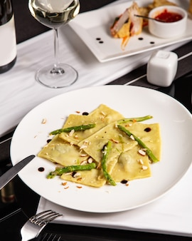 Ein teller mit italienischen ravioli, garniert mit spargel