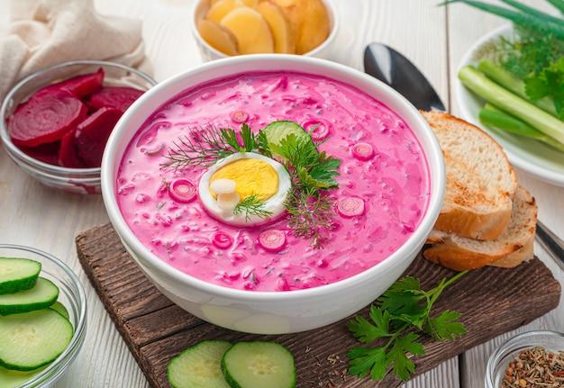 Ein teller mit kalter rote-bete-suppe mit ei und kräutern auf hellem hintergrund. nahaufnahme.