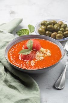 Ein teller mit kalter suppe in form von püriertem gazpacho und oliven mit einem löffel. traditionelles spanisches gericht aus ausgewogenen tomaten, paprika, knoblauch mit einer olivfarbenen serviette