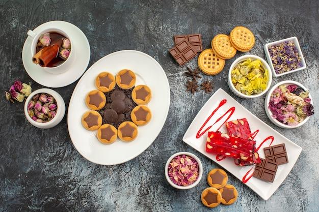 Ein teller mit keks und schokolade mit einer tasse kräutertee und trockenen blumen auf grau