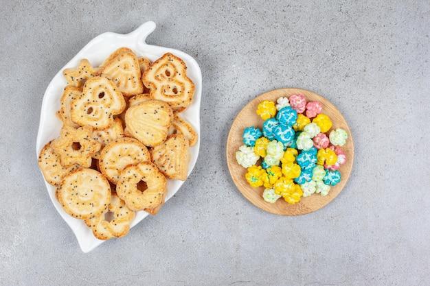 Ein teller mit kekschips und eine handvoll popcorn-bonbons auf marmorhintergrund. hochwertiges foto