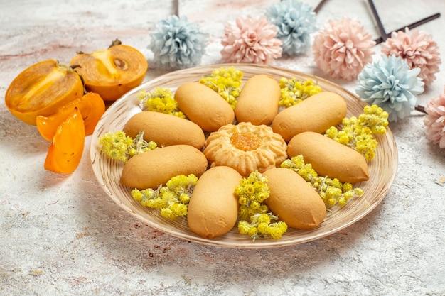 Ein teller mit keksen und palmen und hellblauen und rosa blumen auf weiß