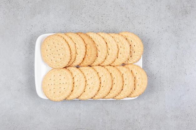 Ein teller mit knusprigen keksen auf marmorhintergrund. hochwertiges foto