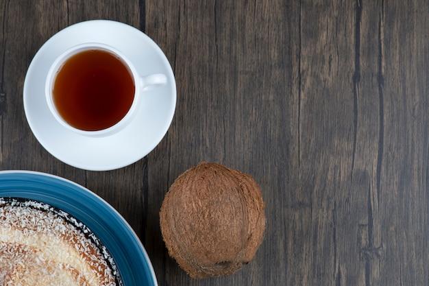 Ein teller mit köstlichem kuchen mit frischer ganzer kokosnuss auf einem holztisch.