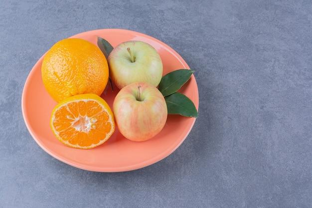 Ein teller mit leckeren äpfeln und orangen auf der dunklen oberfläche