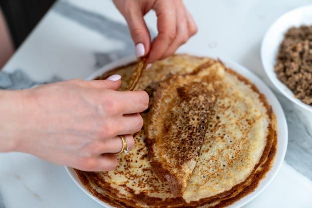 Ein teller mit pfannkuchen und weiblichen händen, die die füllung hineinschrauben