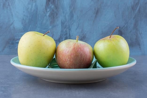 Ein teller mit reifen äpfeln und blättern auf der dunklen oberfläche