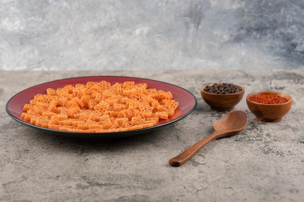 Ein teller mit roher pasta in herzform mit pfeffer auf schwarzem tisch