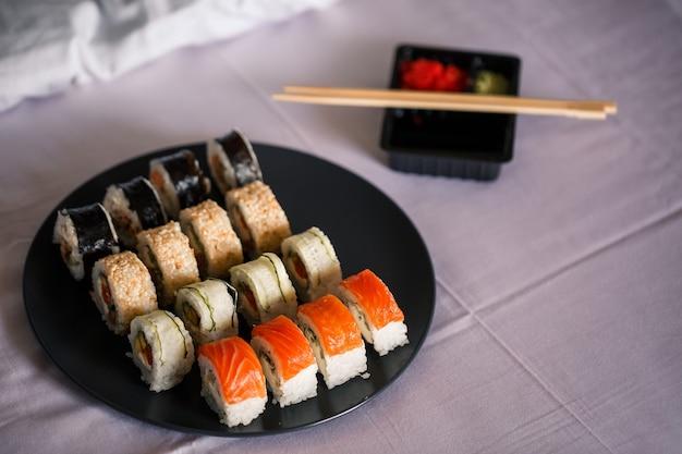Ein teller mit sushi-set steht auf einer weißen tagesdecke, brötchen für ein romantisches abendessen. traditionelles japanisches essen