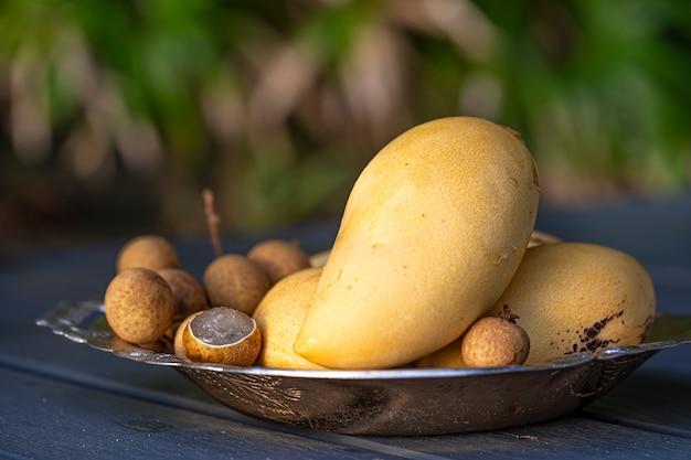 Ein teller mit tropischen früchten auf einem holztisch. gelbe mango und litschi auf unscharfem hintergrund.