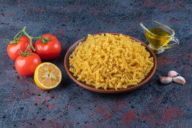 Ein teller mit ungekochten spiralnudeln mit öl und frischen roten tomaten auf einer dunklen oberfläche.