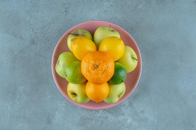 Ein teller mit verschiedenen früchten, auf dem marmorhintergrund. foto in hoher qualität