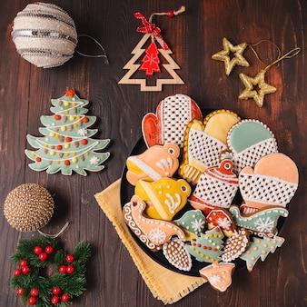 Ein teller mit weihnachtslebkuchen und dekorationen auf braunem holzhintergrund, flach gelegen.