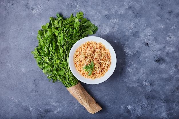 Ein teller pasta auf blauem tisch.