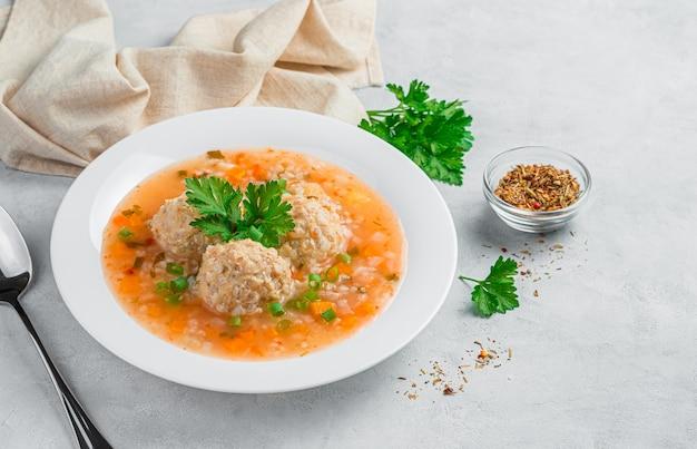Ein teller suppe mit fleischbällchen und reis auf grauem hintergrund mit dill und gewürzen. gesundes essen.