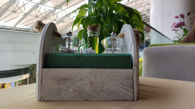 Ein tisch in einem café oder restaurant. servietten in einem hölzernen serviettenhalter, gewürzsalz und pfeffer, olivenöl und soße auf dem tisch.
