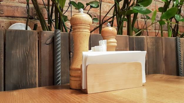 Ein tisch in einem café oder restaurant. weiße servietten in einem holzhalter, salz und pfeffer auf einem holztisch. pizzaständer mit gewürzen, servietten und zahnstochern.