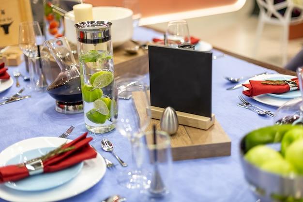 Ein tisch mit blauer tischdecke wird festlich serviert, es gibt stahlgeräte und einen salzstreuer, einen weißen und blanken teller mit einer roten serviette, eine karaffe gefüllt mit kalkwasser und einen schwarzen teller zum nachmachen
