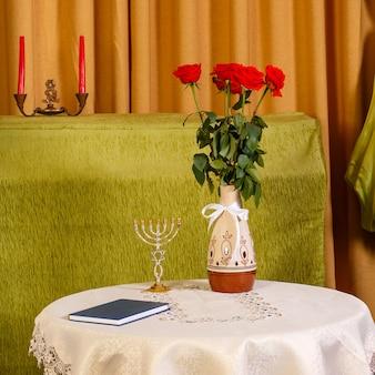 Ein tisch mit blumen und einer menora in der halle für die chupa-zeremonie