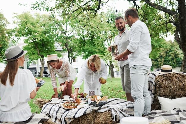 Ein tisch mit getrocknetem heu sorgt für gute laune. eine gruppe erwachsener freunde ruht sich zum abendessen im hinterhof des restaurants aus und unterhält sich.