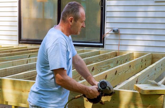 Ein tischler, der auf eine installierung des hölzernen plattformpatios hämmert
