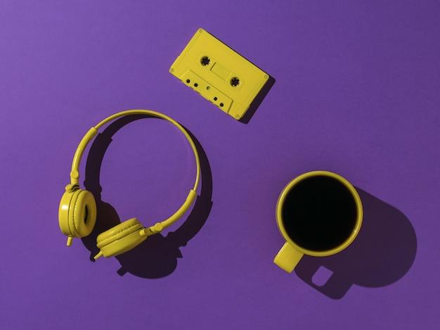 Ein tonbandgerät, gelbe kopfhörer und eine tasse frischen schwarzen kaffee auf violettem hintergrund. farben-trend.