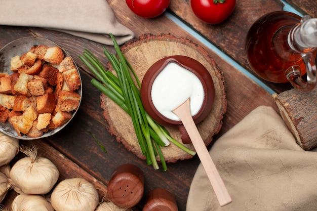 Ein topf joghurt mit kräutern und crackern auf dem holztisch