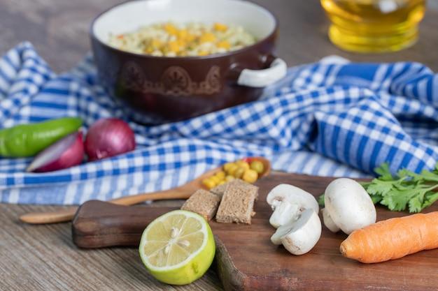 Ein topf mit nudeln mit gemüse und löffel auf tischdecke