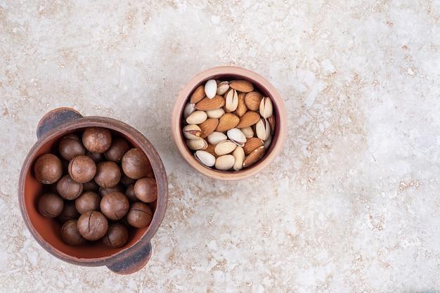 Ein topf mit schokoladenbällchen und eine kleine schüssel mit verschiedenen nüssen